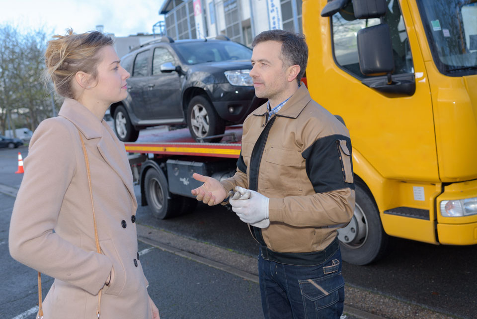 A good tow truck driver reassuring an anxious person
