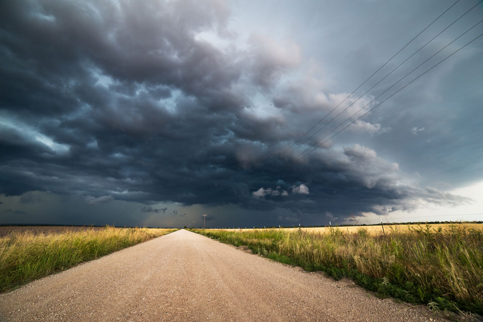 A dirt road with bad weather on the horizon