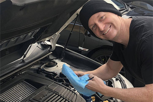 A person texting a car's oil in an effort to make the motor run smoother.