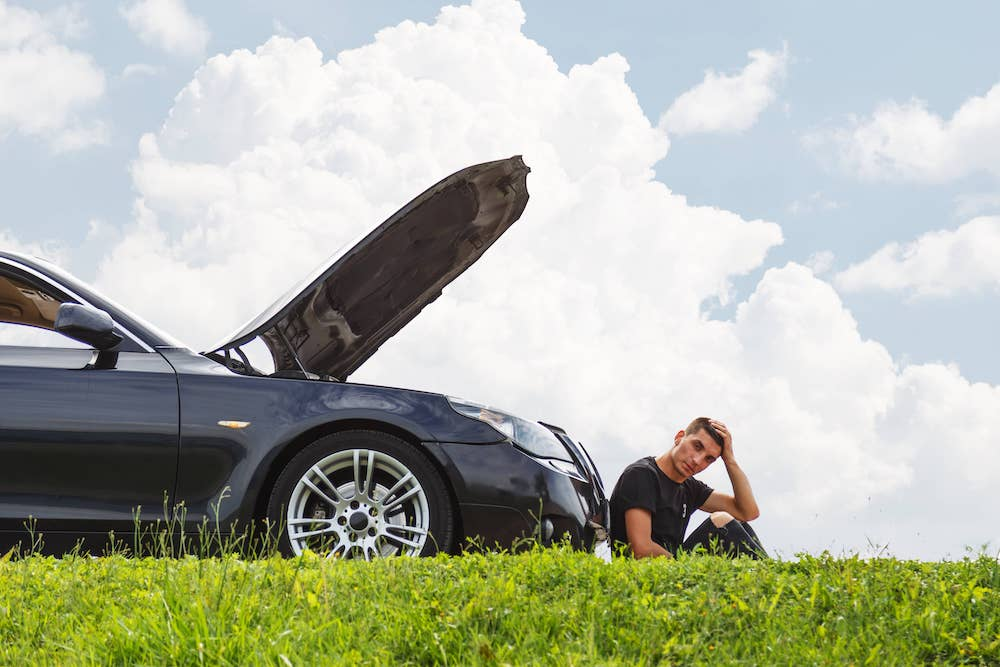 A young man leading up against his broken down car next to green grass while he figures out what to do.