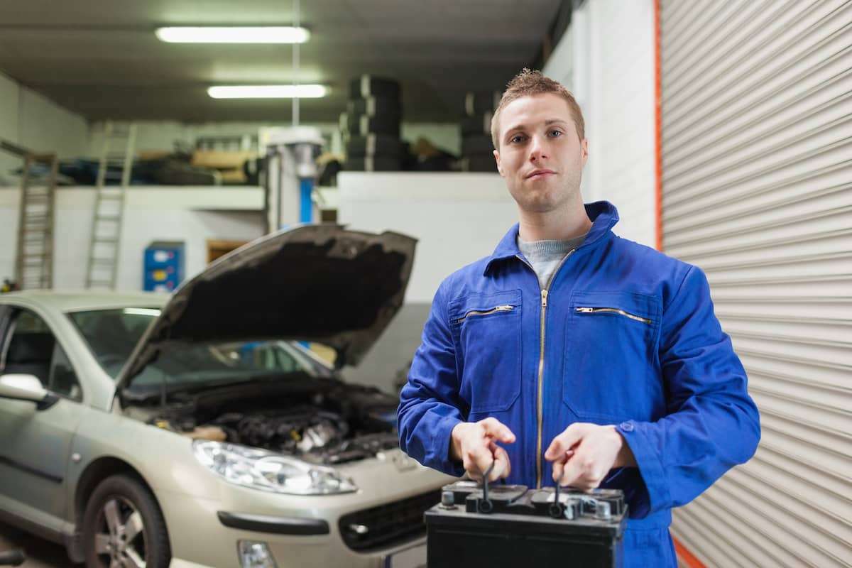 A mechanic standing in a garage holding a car battery.