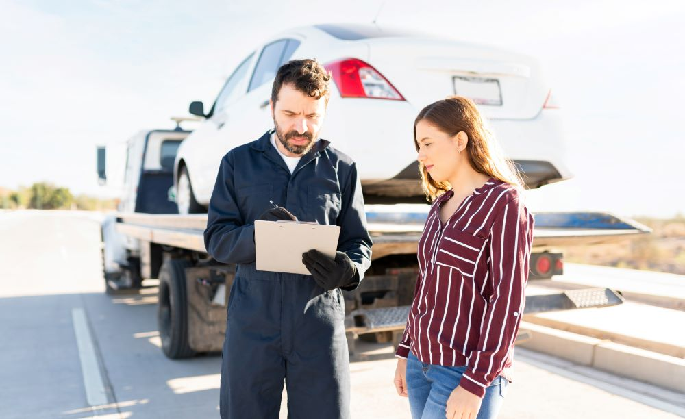 Tow truck driver showing invoice to customer.
