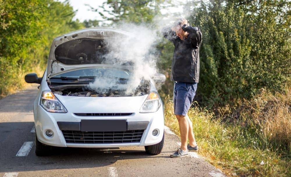 Man checking looking at smoking car engine.